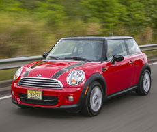 Red MINI Cooper Hardtop with black racing stripes and a black roof