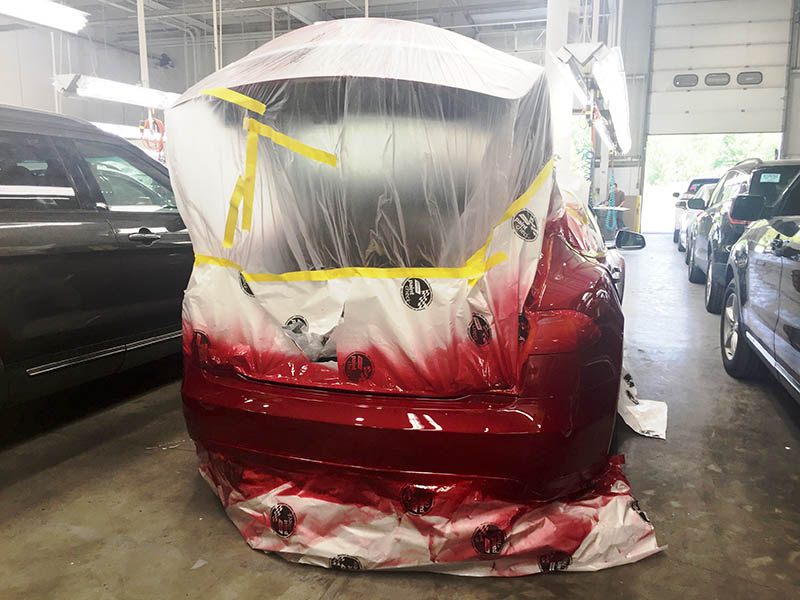 A Tesla Model X has its rear bumper resprayed before heading to the auction line.
